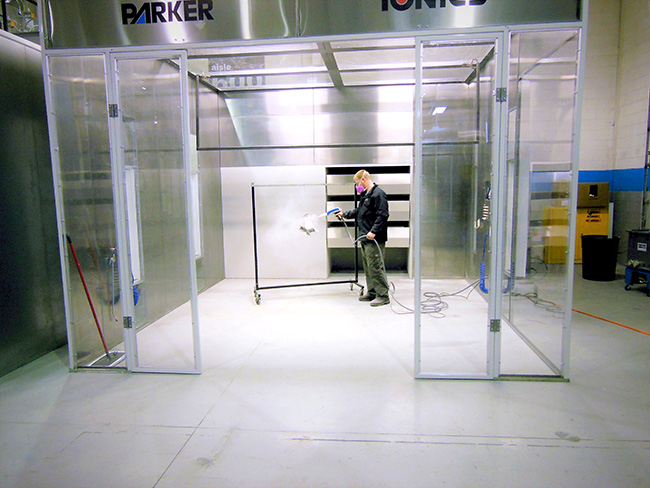 Powder Coating Hoppers - Parker Ionics - attachment_D1_-_Spraying_on_part_hanging_on_rack_in_booth_1